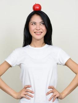 Gelukkige jonge mooie aziatische vrouw die met appel bovenop hoofd denkt