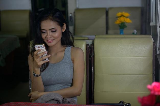 Gelukkige jonge mooie aziatische vrouw die telefoon met behulp van bij de koffiewinkel