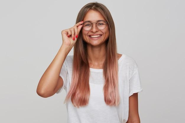 Gelukkige jonge mooie blonde vrouw die haar bril vasthoudt terwijl ze positief kijkt en vrolijk lacht, in een goede bui is terwijl ze over een witte muur staat