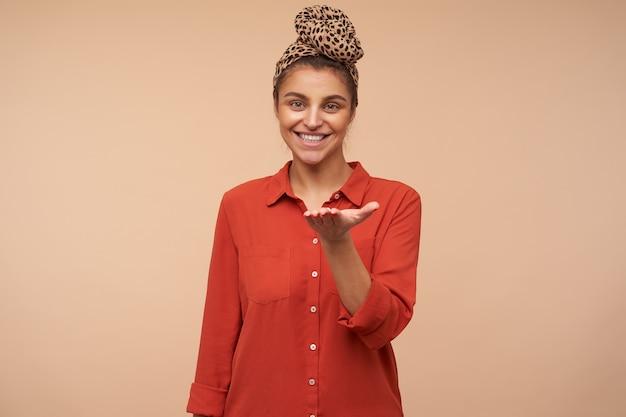 Gelukkige jonge mooie brunette dame met natuurlijke make-up voorzijde met charmante glimlach kijken en verhogen van haar handpalm, poseren over beige muur in rood shirt