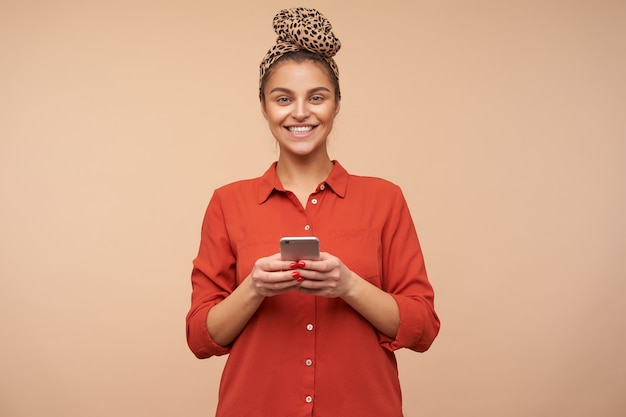 Gelukkige jonge mooie brunette met groene ogen die vrolijk vooraan glimlacht en de smartphone in opgeheven handen houdt terwijl ze over beige muur staat