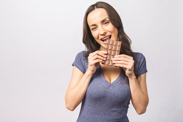 Gelukkige jonge mooie dame die chocolade eet en glimlacht