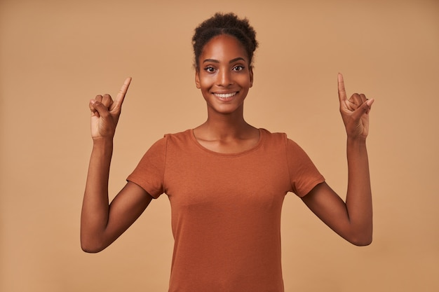 Gelukkige jonge mooie donkerbruine vrouw die haar handen omhoog houdt terwijl ze naar boven wijst en wijd lacht, staande op beige