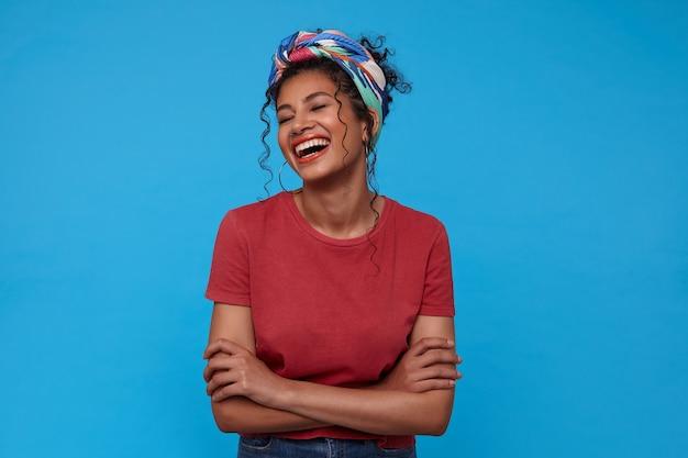 Gelukkige jonge mooie donkerharige vrouw met verzameld haar die haar hoofd naar achteren gooit terwijl ze vrolijk lacht, staande over de blauwe muur met gevouwen handen