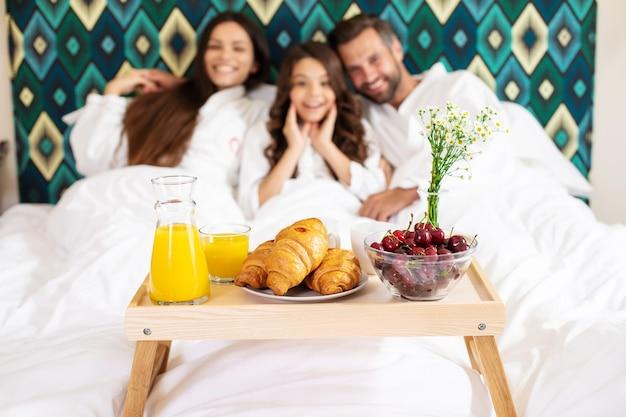 Gelukkige jonge mooie familie in badjassen nemen 's ochtends ontbijt in een luxe hotelkamer