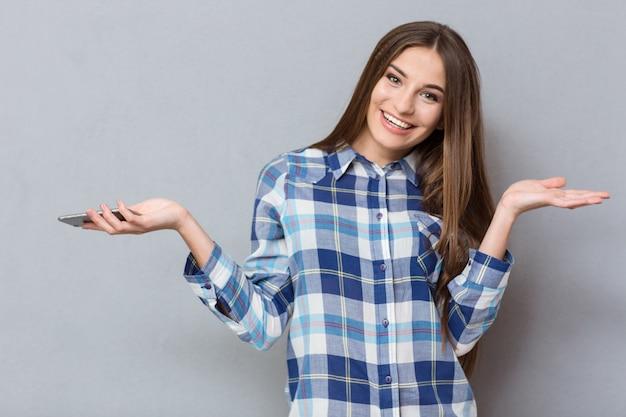 Gelukkige jonge, mooie glimlachende vrouw met kong-haar in geruit hemd met mobiele telefoon en copyspace op de handpalmen