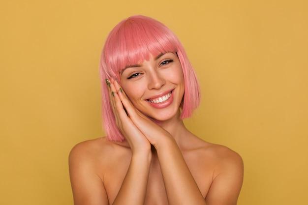 Gelukkige jonge mooie kortharige dame met natuurlijke make-up die opgeheven handen samen vouwt en wang erop leunt, vreugdevol glimlachend terwijl poseren over mosterdmuur