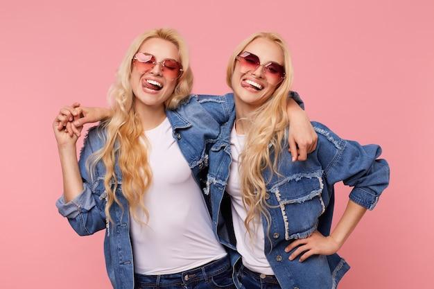 Gelukkige jonge mooie langharige blonde dames gekleed in vrijetijdskleding lachen gelukkig terwijl ze elkaar omhelzen, staande tegen een roze achtergrond