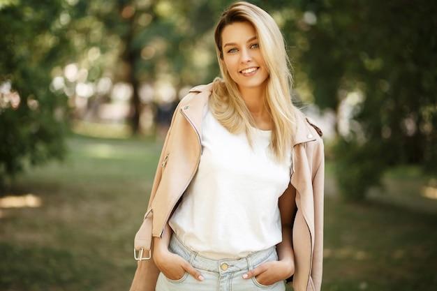 Gelukkige jonge mooie modelvrouw in modieuze roze jasje buitenaard