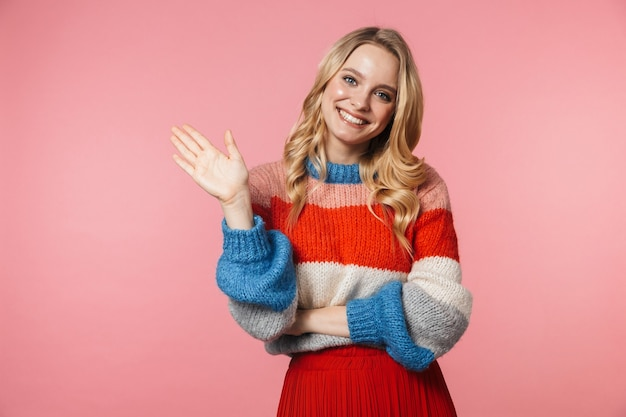 Gelukkige jonge mooie mooie vrouw poseren geïsoleerd over roze muur zwaaien