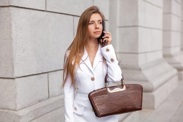 Gelukkige jonge mooie onderneemster die een modieuze zak houdt, die op telefoon spreekt