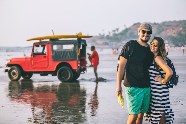 Gelukkige jonge mooie paar man en vrouw op het strand op het strand op de achtergrond van de jeep