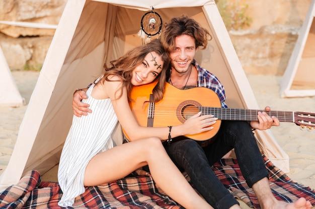 Gelukkige jonge mooie paar zitten met gitaar op het strand bij de tent