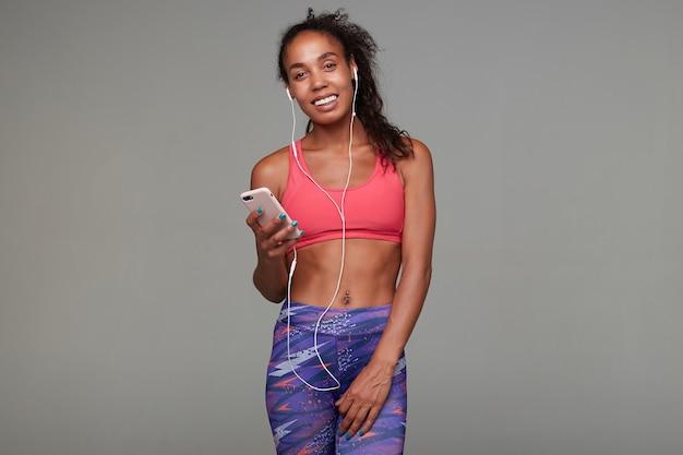 Gelukkige jonge mooie sportieve donkere vrouw met bruin krullend haar smartphone in haar hand houden en vrolijk glimlachen terwijl ze naar muziek luistert