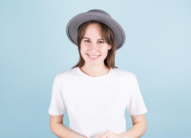 Gelukkige jonge mooie vrouw die grijze hoed met wit overhemd draagt, camera bekijkt en over blauwe achtergrond glimlacht.