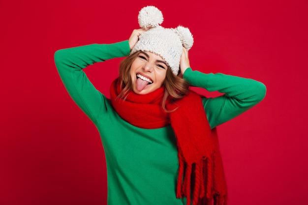 Gelukkige jonge mooie vrouw die hoed en warme sjaal draagt