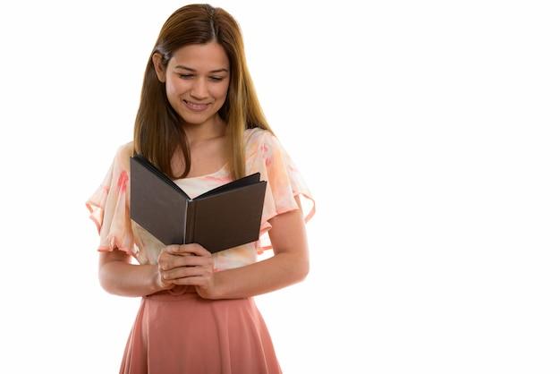 Gelukkige jonge mooie vrouw die lacht tijdens het lezen van boek