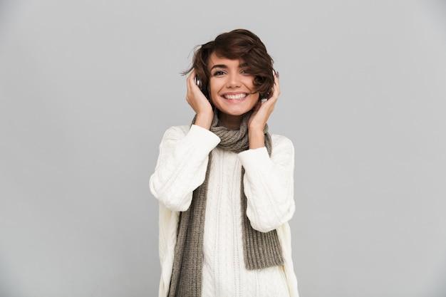Gelukkige jonge mooie vrouw die sjaal geïsoleerde status draagt