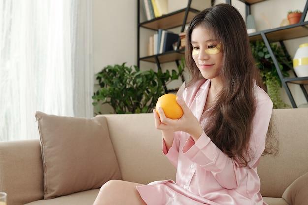 Gelukkige jonge mooie vrouw die verse sinaasappel pelt voor het ontbijt wanneer ze na het wakker worden op de bank in pyjama zit