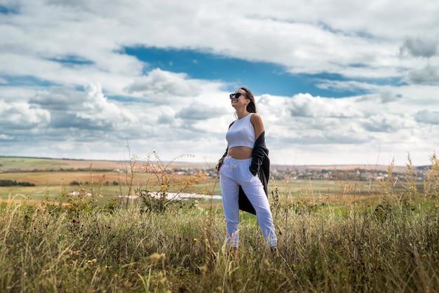Gelukkige jonge mooie vrouw genieten van het landschap in de buurt van groen veld in de zomer