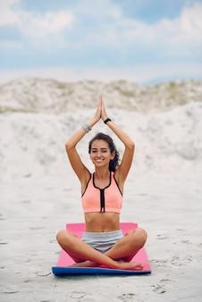 Gelukkige jonge mooie vrouw het praktizeren yoga op het strand bij zonsondergang