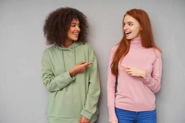 Gelukkige jonge mooie vrouwen die met opgeheven wijsvingers op elkaar wijzen en vrolijk glimlachen, in goede stemming zijn terwijl zij tegen grijze muur staan