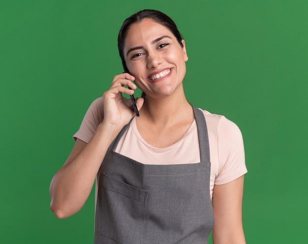 Gelukkige jonge mooie vrouwenkapper die in schort voorzijde glimlachen bekijkt terwijl het spreken op mobiele telefoon die zich over groene muur bevindt
