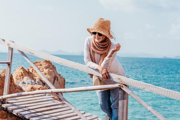 Gelukkige jonge moslim aziatische vrouw die van houten brug kijkt.
