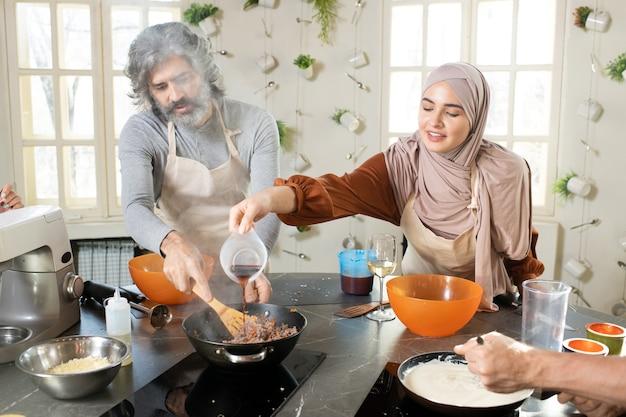 Gelukkige jonge moslimvrouw in hijab die saus in gehakt in koekenpan giet terwijl ze volwassen man in schort helpt met vulling voor gebak