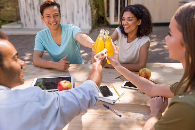 Gelukkige jonge multi-etnische vriendenstudenten die in openlucht sap drinken