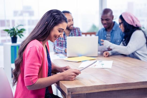Gelukkige jonge onderneemster die digitale tablet gebruiken op kantoor