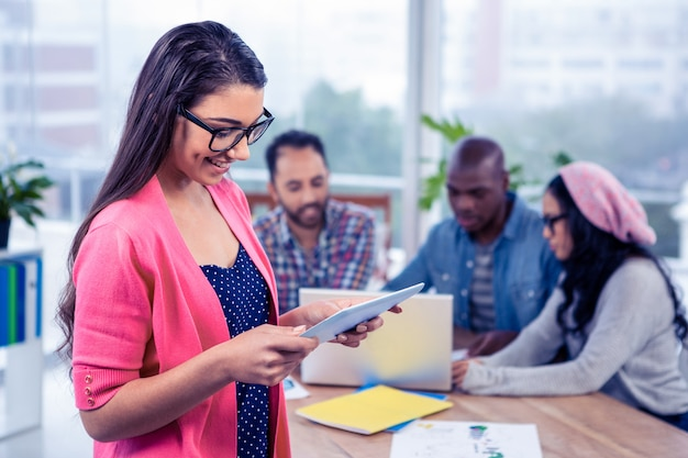 Gelukkige jonge onderneemster die digitale tablet gebruiken terwijl status op kantoor