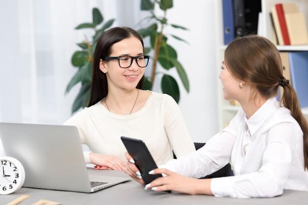 Gelukkige jonge onderneemsterzitting op het werk met digitale tablet en laptop in het bureau