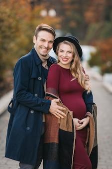Gelukkige jonge ouders een stijlvolle man in een regenjas en een zwangere jonge vrouw in rode jurk en fashiona...