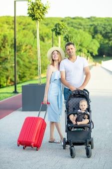 Gelukkige jonge ouders mama en papa met een rode koffer en een baby in een kinderwagen gaan in de zomer op vakantie, glimlachend