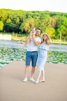 Gelukkige jonge ouders mama en papa met hun zoontje lopen in de zomer door het water aan zee aan de kade en hebben plezier, glimlach