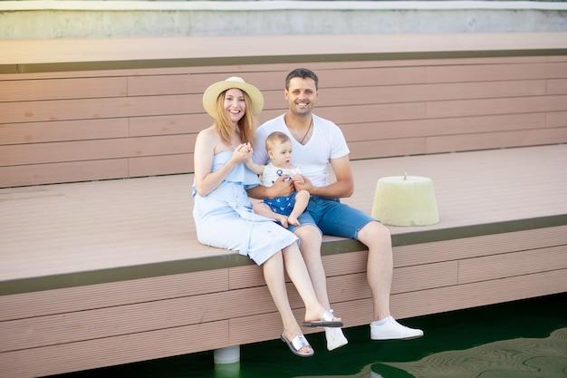 Gelukkige jonge ouders mama en papa met hun zoontje lopen in de zomer door het water aan zee aan de kade en hebben plezier
