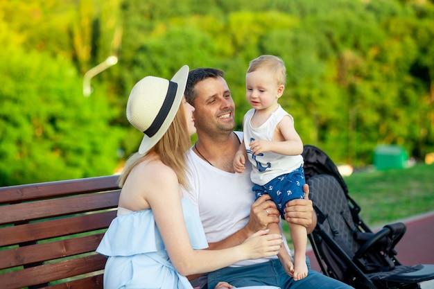 Gelukkige jonge ouders, mama en papa met hun zoontje lopen in het park in de zomer op een bankje en hebben plezier en glimlachen