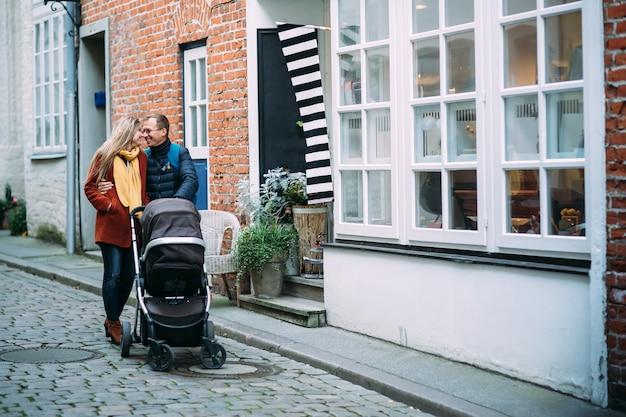 Gelukkige jonge ouders met babywandelwagen in de straat van lübeck (duitsland)