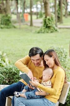 Gelukkige jonge ouders tijd doorbrengen met hun zoontje in park, zittend op een bankje en interessant boek tonen aan kind