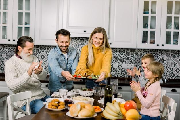Gelukkige jonge ouders, vrouw en man, die gebraden kip aanbiedt aan familie, kinderen en grootvader, met een etentje thuis