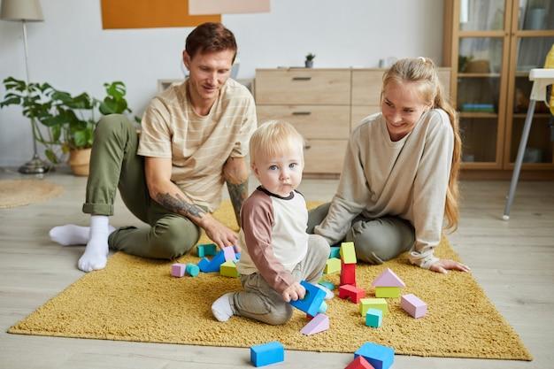 Gelukkige jonge ouders zittend op de vloer en spelen samen met hun zoon in speelgoed in de woonkamer
