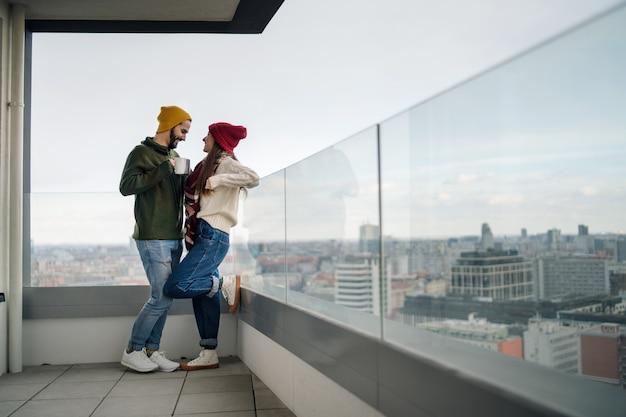 Gelukkige jonge paar eigenaren met koffie op balkon in nieuwe flat verhuizen naar nieuw huis