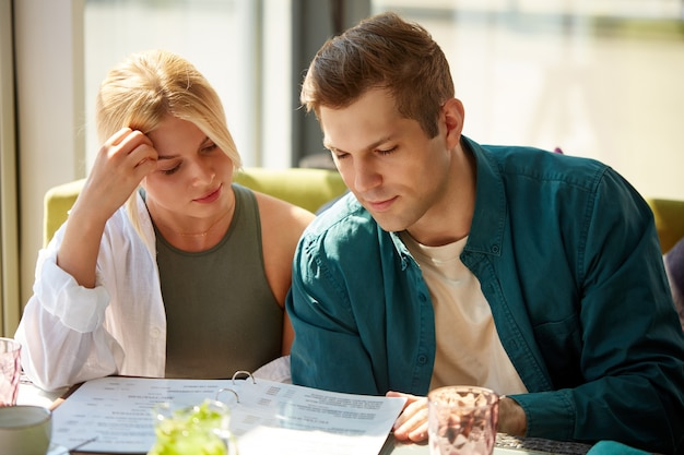 Gelukkige jonge paar genieten tijdens het kiezen van een bestelling uit het menu in het moderne café