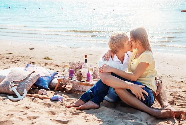 Gelukkige jonge paar genieten van picknick op het strand en hebben goede tijd op zomervakanties