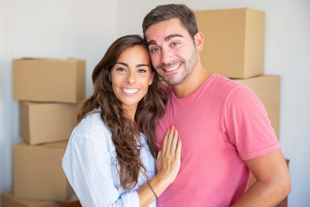 Gelukkige jonge paar genieten van verhuizen naar nieuwe flat, staande tussen kartonnen dozen, knuffelen en camera kijken