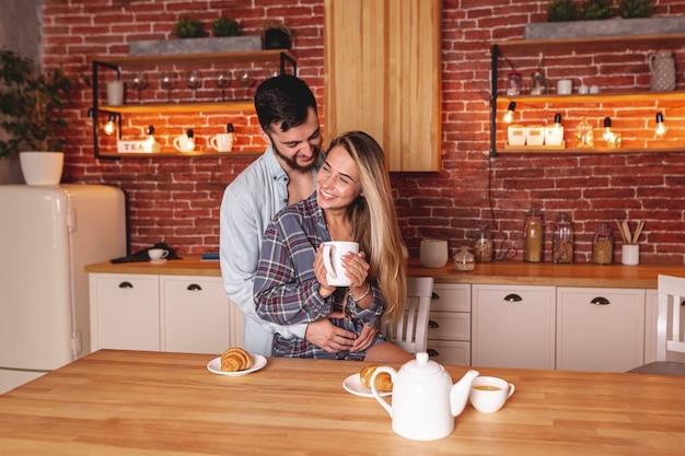 Gelukkige jonge paar het drinken thee bij de keuken
