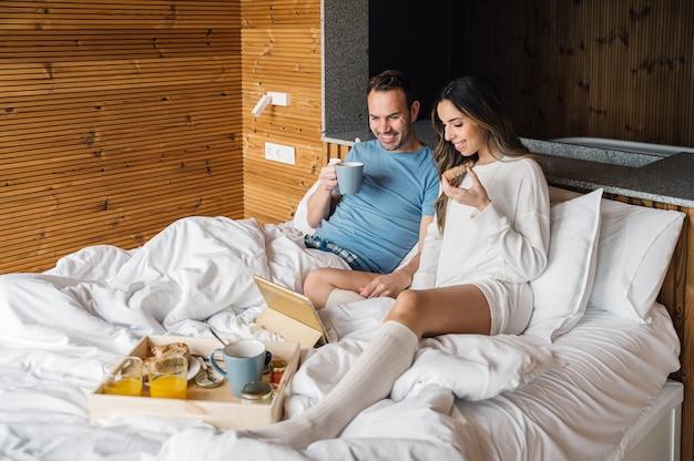 Gelukkige jonge paar in nachtkleding genieten van ontbijt op bed kijken naar film op tablet samen in gezellige slaapkamer met houten muur