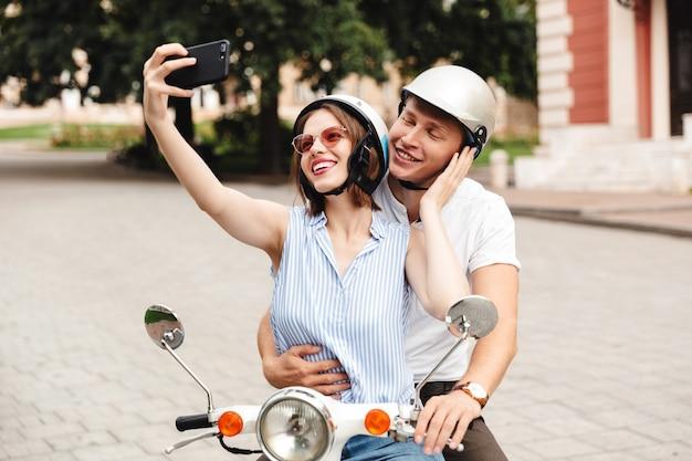 Gelukkige jonge paar in valhelmen selfie maken op smartphone zittend samen op scooter buitenshuis