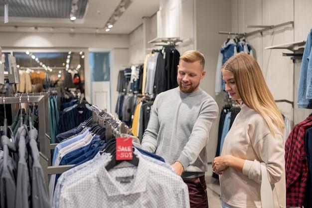Gelukkige jonge paar in vrijetijdskleding die door rek met overhemden op korting staan en nieuwe kiezen tijdens verkoop